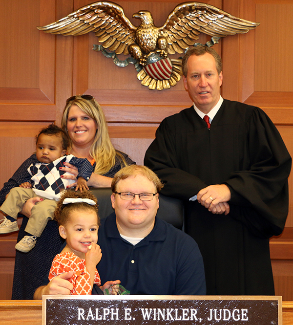The Hensons, Oliver, Alicia, Ella and Rob, pose with Judge Ralph E. Winkler after Oliver's adoption ceremony on Monday, Oct. 3, 2016.